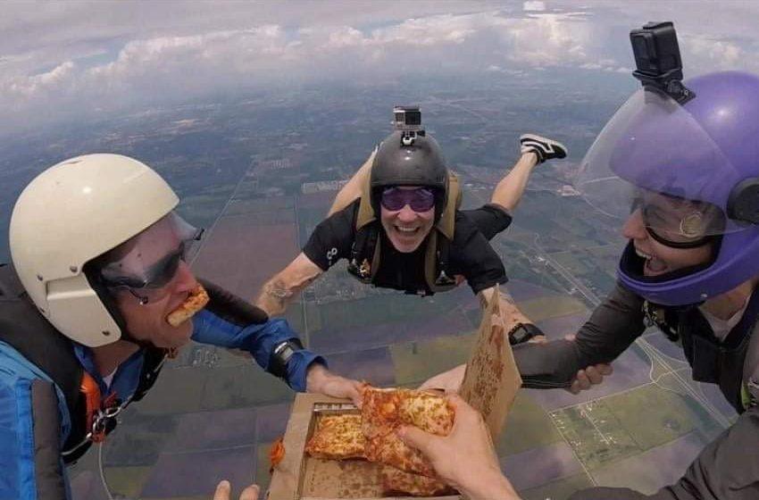 فريق من المظلين يتناول شرائح البيتزا في السماء.